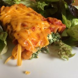 Spinach and ricotta canneloni topped with cheese and served with salad