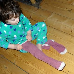 Boy pulling on long socks