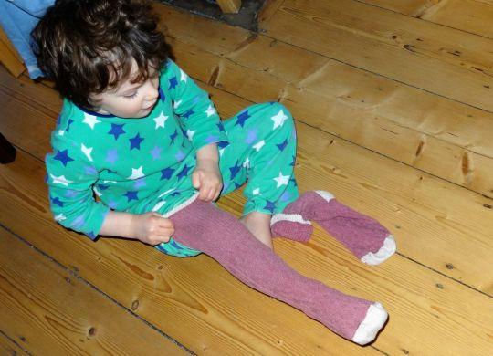 Boy pulling on long socks