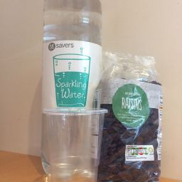 Sparkling water in a bottle, empty plastic cup and a large bag of raisins