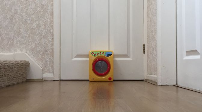 Toy washing machine by internal white door