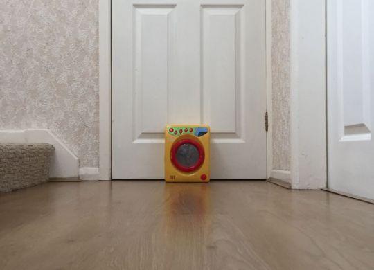 Toy washing machine by internal white door