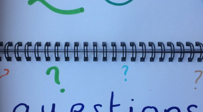The words 'twenty questions' written on a notepad