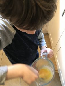 Boy beating egg in jug