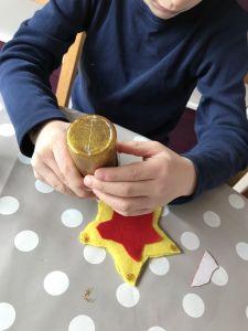 Adding glitter glue to a felt star