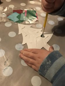 Boy pasting glue on a cardboard Christmas tree