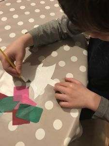Boy pasting glue onto a cardboard Christmas tree