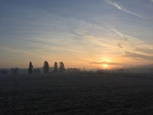 Sunrise on the horizon across fields